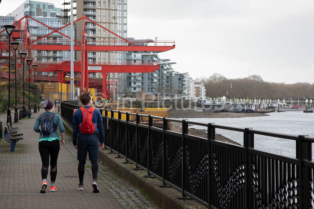 Joggers running along the Thames Path near to the Cringle Dock Solid Waste Transfer Station on 1st February 2020 in London, England, United Kingdom. Waste transfer stations are facilities where municipal solid waste is unloaded from collection vehicles and briefly held while it is reloaded onto larger long-distance transport vehicles for shipment to landfills or other treatment, recycling or disposal facilities.
