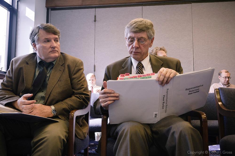 Legislative aids check their notes during a Democratic party caucus at the Alaska State Legislature.