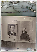 reproduction of portraits on a severely eroding glass plate of a young male and senior female photograph