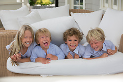 four siblings laughing while on a couch on a porch