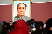 """Visitors walk under a portrait of Mao Zedong (Mao Tse-tung) at the Tiananmen Square in Beijing, China, on 10 December 2011.  Tiananmen Square is considered the symbolic center of all China, it's significance is not lost on China's current leaders as it tightens its security and surveillance of the area to spot potential """"trouble makers"""""""