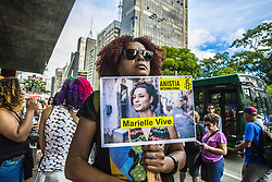 April 14, 2018 - Sao Paulo, Sao Paulo, Brazil - People gather in Paulista Avenue, Sao Paulo, Brazil on April 14, 2018 during a demonstration marking one month of activist Marielle Franco's murder. The murder of Franco, a black Brazilian activist who fought her way out of the slums to become a popular councilor, made headlines around the world. The outspoken 38-year-old, who was a critic of police brutality, an advocate for minorities and the posterchild of a new type of politics, was shot dead on March 14 in an assassination-style killing with four bullets to the head. (Credit Image: © Cris Faga/NurPhoto via ZUMA Press)