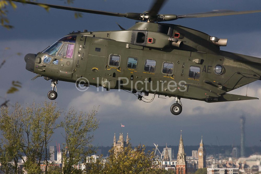 An AgustaWestland AW101 makes a controlled landing in a south London public park below. The houses of Parliament are in the distance. After circling for 5 minutes in windy conditions and hovered metres above the ground n Ruskin Park, south London. Autumn leaves flew in all directions in this regular landing point for the Royal Air Force and army. The RAF frequently make reconnaissance flights to this Lambeth open space for crew training purposes. The Merlin is a medium-lift helicopter used in both military and civil applications. It was developed by joint venture between Westland Helicopters in the UK and Agusta in Italy and was named the EH101 until 2007.