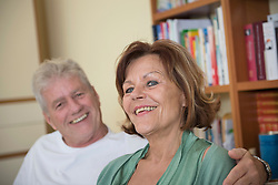 Portrait of senior couple sitting on couch in living room, smiling