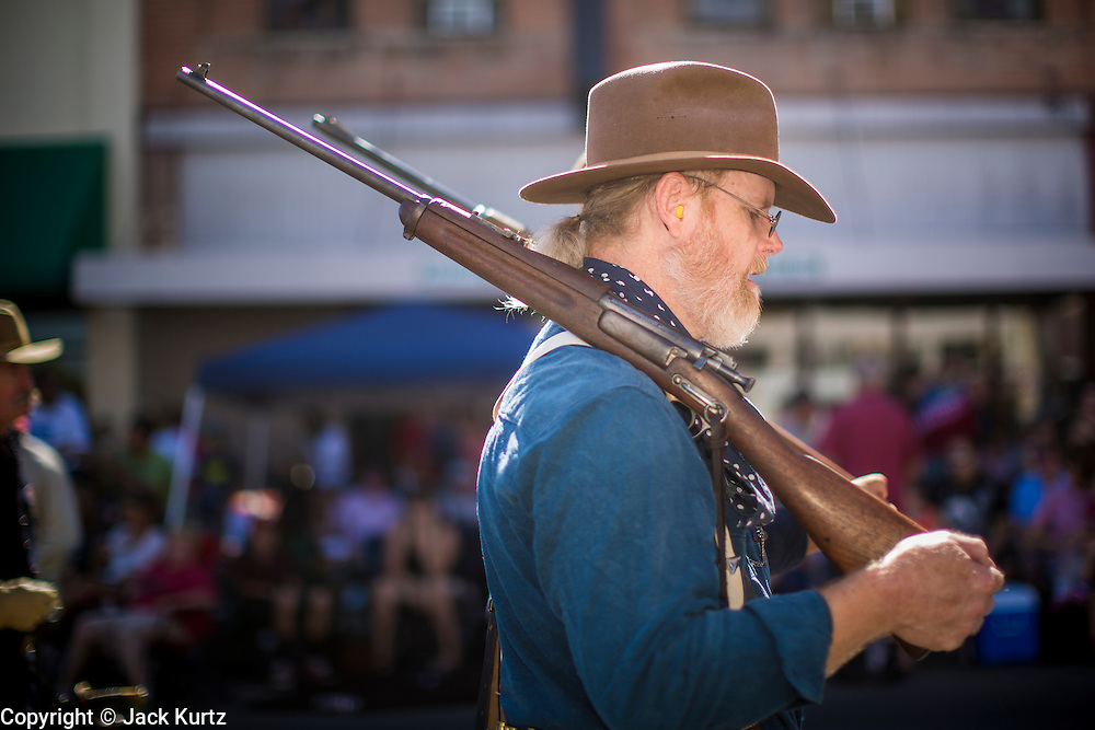 30 JUNE 2012 - PRESCOTT, AZ:  A member of the Rough Riders reenactors carries a .30-40 Krag carbine in the Prescott Frontier Days Rodeo Parade. Several prominent Arizonans were members of the Rough Riders in the Spanish American War and the Rough Riders feature prominently in Arizona history. The parade is marking its 125th year. It is one of the largest 4th of July Parades in Arizona. Prescott, about 100 miles north of Phoenix, was the first territorial capital of Arizona.    PHOTO BY JACK KURTZ