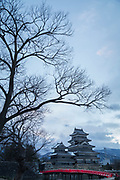 Majestic castle against cloudy sky captured from low angle, Matsumoto, Japan