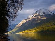 Breaking storm sunlight illuminating fall vegetation above Bowman Lake with Square Peak and Rainbow Peak beyond, Glacier National Park, Montana.