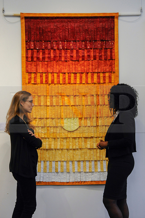 """© Licensed to London News Pictures. 12/05/2017. London, UK.   Staff members stand in front of """"Composition No. 25 (Soleil)"""", 2015, by Abdoulaye Konaté (Mali) (Est. GBP 10-15k) at the preview for the first sale dedicated to Modern and Contemporary African Art at Sotheby's New Bond Street.  The sale features over 115 artworks by over 60 different artists from 14 countries across the continent. Photo credit : Stephen Chung/LNP"""