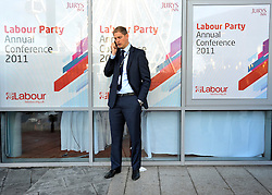 © Licensed to London News Pictures. 27/09/2011. LONDON, UK. A delegate on a phone outside the Jury's Inn hotel at The Labour Party Conference in Liverpool today (27/09/11). Photo credit:  Stephen Simpson/LNP