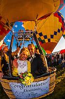 Just married couple taking off for a hot air balloon flight during the Albuquerque International Balloon Fiesta, Albuquerque, New Mexico USA.
