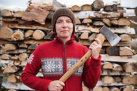 Female hiker in nordic style sweater holding axe to cut firewood at mountain hut, Kungsleden trail, Lappland, Sweden