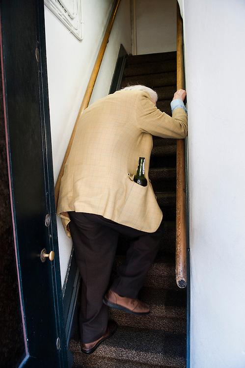 Nederland, Amsterdam, 21 april 2011. .Oude gaat zijn woning binnen in het centrum van amsterdam..Hij komt van Albert Heijn en heeft in beide zakken van zijn nette colbert drankflessen...Foto (c)  Michiel Wijnbergh