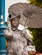Mime artist, stone statue of woman in period clothing with umbrella, Buenos aires, Argentina.