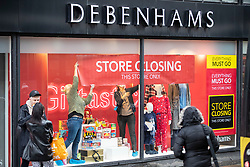 © Licensed to London News Pictures. 02/12/2020. Manchester, UK. Workers hang up sale signs in the windows of Debenhams in Manchester as the city enters Tier 3 restrictions.  Photo credit: Kerry Elsworth/LNP
