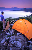 Young man and dog camping above Lake Tahoe, CA.<br />