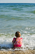A girl sits in the sand as waves crash around her.