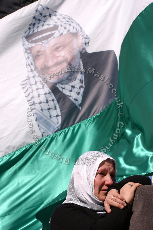 Palestinian woman crying in front of a Palestinian flag portraying a picture of former Palestinian leader Yasser Arafat at the Palestinian Authority (PA) headquarter, last residence and burial site of Yasser Arafat, in the Palestinian capital Ramallah, on Friday, Nov. 11, 2005. Here a mausoleum and a museum in his honour will be built soon. **ITALY OUT**
