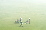 © Licensed to London News Pictures. 14/04/2015. Seaford, UK. Golfers carry on their game in the mist.  People in the early morning sea mist and sunshine in Seaford today 14th April 2015. Today is expected to be a very warm day across Britain. .. Photo credit : Stephen Simpson/LNP