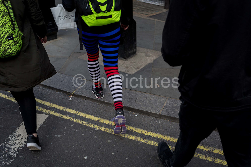 A womans legs in striped leggings walk across the kerb of a central London street, on 28th March, 2017, in London, England.