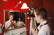 The Lasceve family: brother tying his tie in the bathroom mirror as his sister watches. Paris, France.