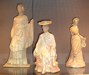 Left to right: Terracotta figure of a woman.  Made in Athens about 220-180 BC  Said to be from Tanagra.     Terracotta figure of a young man seated on a rock.  Made in Boeotia about 300 BC.  Said to be from Tanagre.  The colours are exceptionally well preserved.     Terracotta woman holding a hinged box-mirror.  Made in Boeotia about 230-200 BC.  Said to be