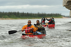 Richard Jeo, a scientist with the Nature Conservancy, front, and Dr. Sanjayan Muttulingam paddle with Dene First Nation youth down the Thelon river In the middle of the largest and most remote game sanctuary in North America, in the Northwest Territories, just south of the Arctic Circle. Its fate now hangs in the balance, protected on paper, but with little management, no money, and no voice for the Dene, its most ardent advocate for protection, while mining (for diamonds, gold, and uranium) threats, buoyed by recent prices, loom.  Dene youth have rarely been deep into the Thelon, yet the caribou is still their life blood, reverentially important.  These Dene are amongst the last hunter/gatherers in the Northern Hemisphere.   (Photo by Ami vitale)