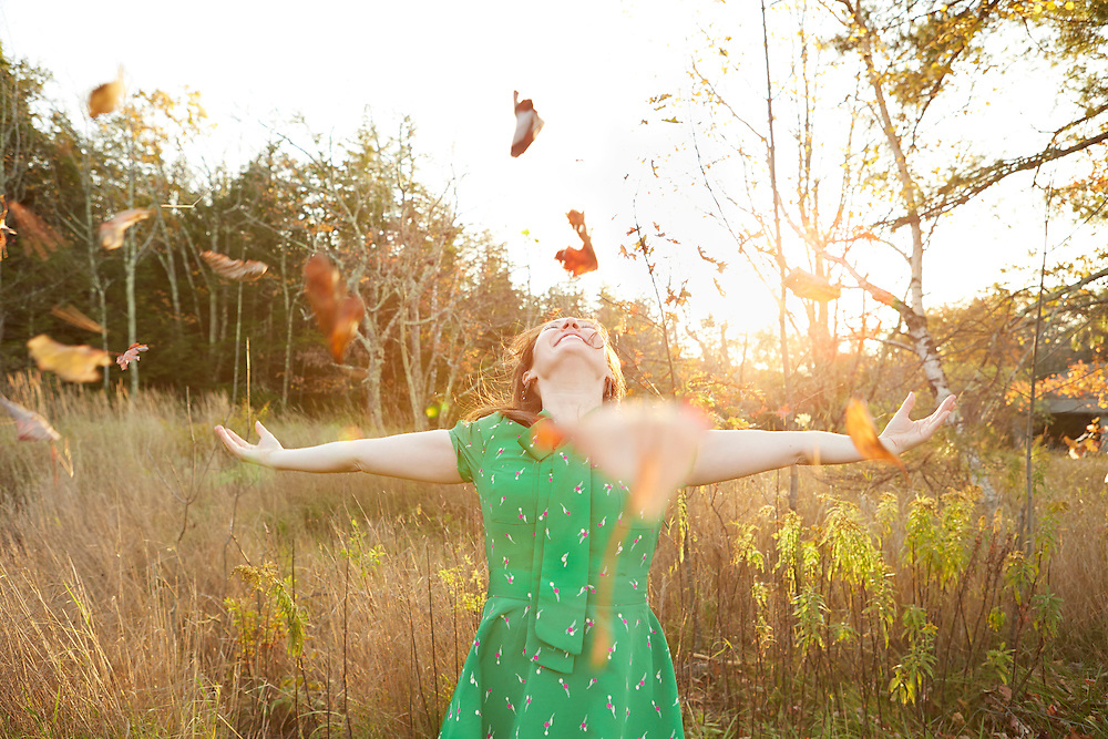 Lifestyle image of ecstatic girl throwing leaves in the air outside during autumn with sun glowing and setting in background