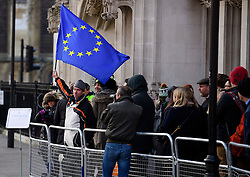 © Licensed to London News Pictures. 05/12/2016. London, UK. A pro EU supporter waves an EU flag the Supreme Court  in Westminster, London as he waits to enter court, for first day of a  Supreme Court hearing to appeal against a November 3 High Court ruling that Article 50 cannot be triggered without a vote in Parliament. Photo credit: Ben Cawthra/LNP