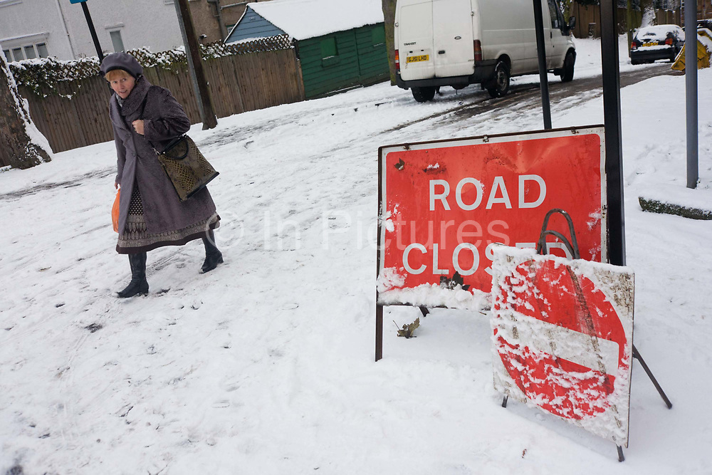 A local lady shopper passes-by a Closed Road sign on a hill in south London during wintry snows. Rather than drive to her local supermarket, the woman has instead parked her car in a safer place and walked to where she can stock up on provisions. She has made her way up the incline from the shop and looks over to the sign telling others that this road is temporily shut to vehicles. During a mid-winter morning, when commuters are struggling to reach their work places, the capital also finds it hard for transport and infrastructure to keep running as normal. Local councils facing government cuts also find it hard to maintain services during such challenging conditions.