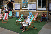 South Londoners enjoy deckchairs outside Herne Hill station during a summer heatwave. A queue of people waiting to obtain cash from an ATM while on two of the chairs a man reading a Saturday tabloid newspaper and another, looking depressed and downtrodden on a day of otherwise festivity when the local Lambeth Show occurs in nearby Brockwell Park in this district of south London.