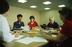Various health workers sitting around table undergoing staff development training at the Queens Medical Centre; Nottingham,