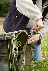Sharpening the blades of a lawn mower with a metal file