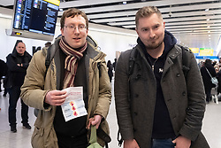 © Licensed to London News Pictures. 22/01/2020. London, UK.British passenger Robert Crosby(L) and brother Thomas Crosby(R) speak to the media at Heathrow airport arriving on China Southern Airlines flight CZ673 from Wuhan arrives in London. He is holding a government health warning. The Coronavirus virus has originated in the Wuhan region. Photo credit: Ray Tang/LNP
