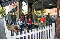 Este, Lindsay and Margaret sit and enjoy coffee and conversation with their children Indy, Campbell, Banyan and Mabel as visitors stream in to the Cafe Monte Alto on Main Street in Plymouth Tuesday morning.   (Karen Bobotas/for the Laconia Daily Sun)