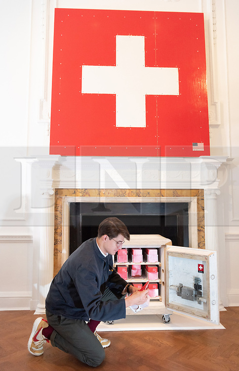 """© Licensed to London News Pictures. 05/10/2018. London, UK. Art installation titled Swiss Passport Office by American artist Tom Sachs. The 24hliveperformanceSwiss Passport Office is on show at the Galerie Thaddaeus Ropac. Those wishing to purchase a passport will be photographed and have their name hand-typed onto a serial-numbered passport issue, stamped with a Studio endorsement and entered into the permanent database. Passports cost €20 (no British pounds will be accepted). Swiss Passport Officeencompasses contemporary concerns relatingto Brexit, Syria and Trump's immigration policies and their challenge to the notion of global citizenship. """"To effect change, we must first imagine the world not the way it is, but the way we want it to be,"""" Sachs says. Photo credit: Ray Tang/LNP"""