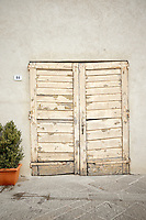 Photo of a rustic doorway in San Quirico d'Orcia, Italy.
