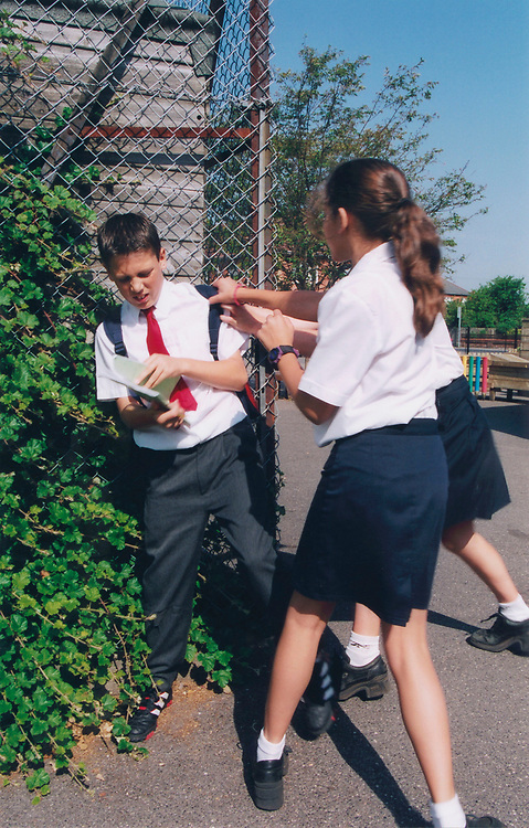 Bullying at school - two girls picking on a boy in the playground, POSED BY MODELS