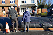 "© Licensed to London News Pictures. 16/02/2014. Chertsey, UK. Neighbours talk over the dam which they affectionately call ""the Sausage"". An Aqua dam has been erected along Bridge Road in Chertsey, Surrey. At almost half a mile long and four feet high the dam is designed to protect 200 houses on the South Side of the street. The Environment Agency has said there is nothing they can do to protect the houses on the North side if flood water from the River Thames rises. . Photo credit : Stephen Simpson/LNP"