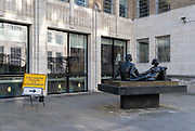 A Covid Testing Centre sign points those requiring a Coronavirus test, past the sculpture entitled Beyond Tomorrow by Karin Jonzen, and around the corner of the Guildhall in the City of London, the capitals financial district, on 9th March 2021, in London, England. Karin Margareta Jonzen, née Löwenadler, 1914 – 1998 was a British figure sculptor whose works, in bronze, terracotta and stone, were commissioned by a number of public bodies in Britain and abroad.