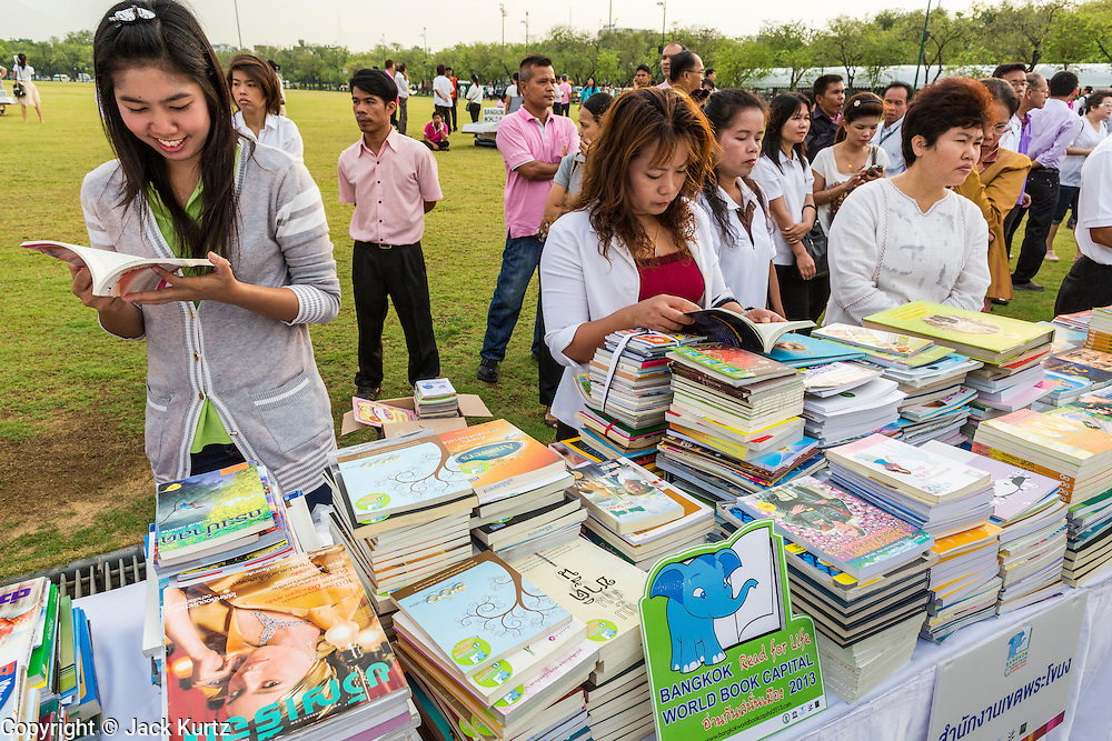 """23 APRIL 2013 - BANGKOK, THAILAND: Thais browse among the books being donated to Thai literacy projects during the opening ceremony to mark Bangkok as the World Book Capital City 2013. UNESCO awarded Bangkok the title. Bangkok is the 13th city to assume the title of """"World Book Capital"""", taking over from Yerevan, Armenia. Bangkok Governor Suhumbhand Paribatra announced plans that the Bangkok Metropolitan Administration (BMA) intends to encourage reading among Thais. The BMA runs 37 public libraries in the city and has modernised 14 of them. It plans to build 10 more public libraries every year. Port Harcourt, Nigeria will be the next World Book Capital in 2014.  .PHOTO BY JACK KURTZ"""