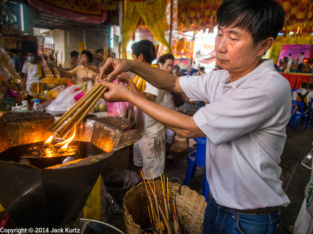 27 SEPTEMBER 2014 - BANGKOK, THAILAND:  A man lights incense during the celebration of the Vegetarian Festival at the Chow Su Kong Shrine in Talat Noi, a Chinese enclave in Bangkok. The Vegetarian Festival is celebrated throughout Thailand. It is the Thai version of the The Nine Emperor Gods Festival, a nine-day Taoist celebration beginning on the eve of 9th lunar month of the Chinese calendar. During a period of nine days, those who are participating in the festival dress all in white and abstain from eating meat, poultry, seafood, and dairy products. Vendors and proprietors of restaurants indicate that vegetarian food is for sale by putting a yellow flag out with Thai characters for meatless written on it in red.   PHOTO BY JACK KURTZ