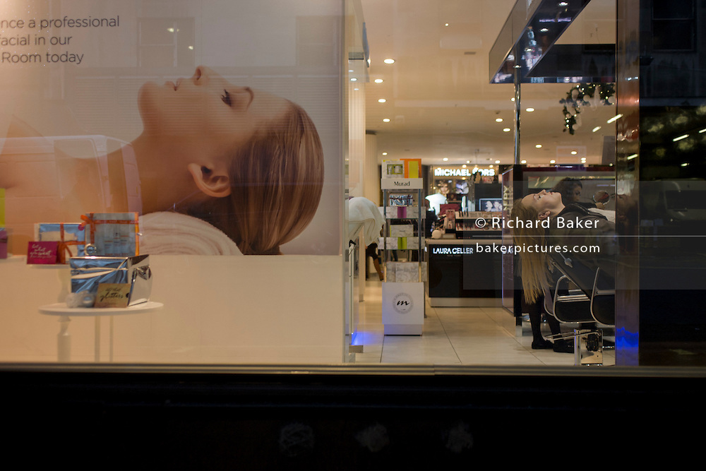 Large image of a model and real-life lady customer also reclined for beauty treatment, in the window of Debenhams on London's Oxford Street.