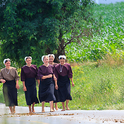 Intercourse, PA, USA - June 26, 2011:  Young Amish women walk bare-foot along a rural, country road in Lancaster County.
