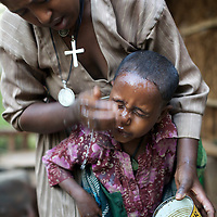 """Wubalem washes her daugher Rekebki's face in the kitchen area at the back of their home.<br /> <br /> Wubalem Shiferaw, age 23, lives in the village of Mecha with her husband Tsega Bekele, age 33, and their daughter Rekebki, age 4. Wubalem remembers her grandparents harvesting honey. She has maintained this tradition while moving to modern hives which produce a far greater yield of honey. Wubalem is a member of the Mecha village Cooperative which brings together local women beekeepers allowing them to share insights and build a credit union. The Mecha village Cooperative is not yet a member of the Zembaba Union. Wubalem's husband Tsega is a priest and a tailor. <br /> <br /> Harvesting honey supplements the income of small farmers in the Ethiopian region of Amhara where there is a long tradition of honey production. However, without the resources to properly invest in production and the continued use of of traditional, low-yielding hives, farmers have not been able to reap proper reward for their labour. <br /> <br /> The formation of the Zembaba Bee Products Development and Marketing Cooperative Union is an attempt to realize the potential of honey production in Amhara and ensure that the benefits reach small producers. <br /> <br /> By providing modern, high-yield hives, protective equipment and training to beekeepers, the Cooperative Union helps increase production and secure a steady supply of honey for which there is growing demand both in and beyond Ethiopia. The collective processing, marketing and distribution of Zembaba's """"Amar"""" honey means that profits stay within the cooperative network of 3,500 beekeepers rather than being passed onto brokers and agents. The Union has signed an agreement with the multinational Ambrosia group to supply honey to the export market. <br /> <br /> Zembaba Bee Products Development and Marketing Cooperative Union also provides credit to individual members and trains carpenters in the production of modern hives. <br /> <br /> Ph"""