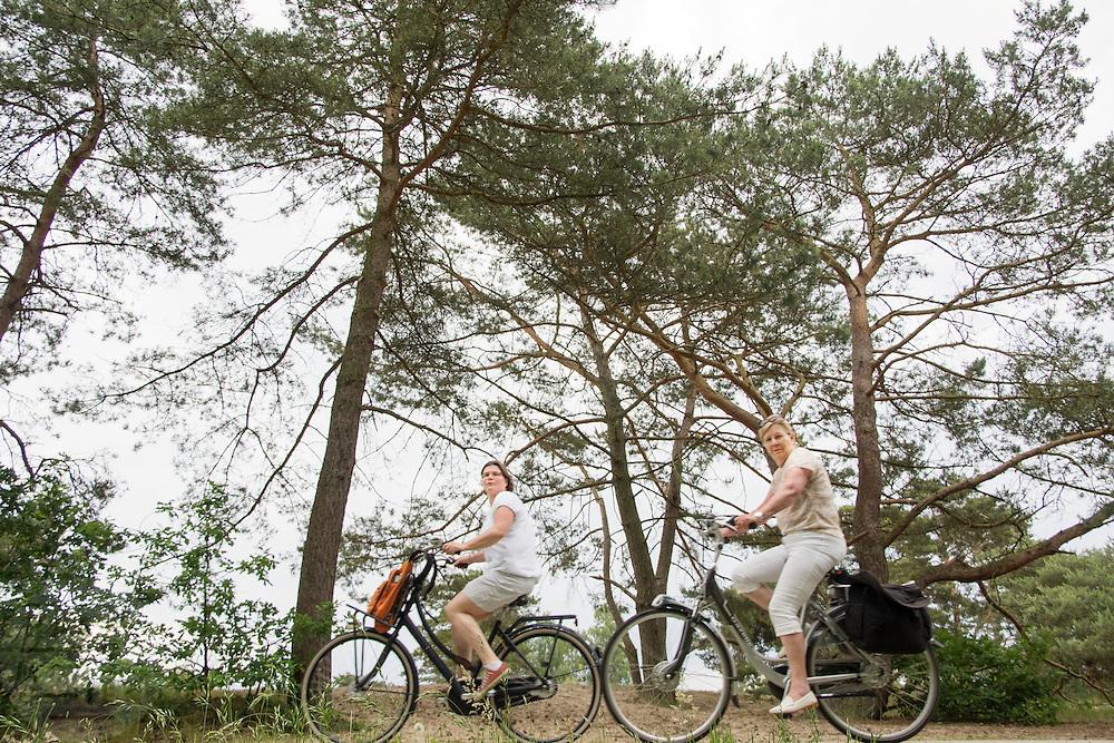 In Soest rijden een twee vrouwen langs de Soesterduinen, een rijdt op een elektrische fiets, de ander op een gewone stadsfiets.<br /> <br /> In Soest a two women are cycling. On of them is riding an e-bike, the other one an ordinary Dutch bike.