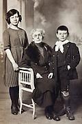 studio portrait of grandmother with children 1900s