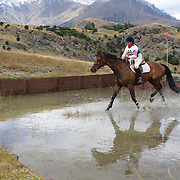 Kristi Doherty riding Zakattack in action at the water jump during the Cross Country event at the Wakatipu One Day Horse Trials at the Pony Club grounds,  Queenstown, Otago, New Zealand. 15th January 2012. Photo Tim Clayton
