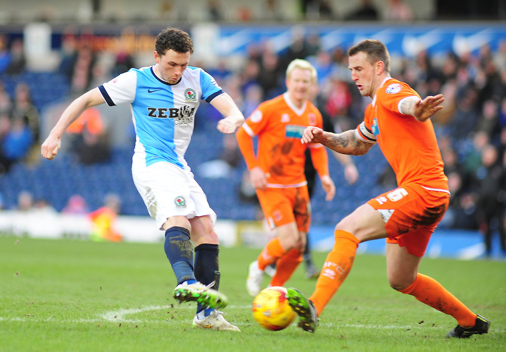 Blackburn's Corry Evans gets a shot away under pressure from Blackpool's Peter Clarke<br /> <br /> Photographer Andrew Vaughan/CameraSport<br /> <br /> Football - The Football League Sky Bet Championship - Blackburn Rovers v Blackpool - Saturday 21st February 2015 - Ewood Park - Blackburn<br /> <br /> © CameraSport - 43 Linden Ave. Countesthorpe. Leicester. England. LE8 5PG - Tel: +44 (0) 116 277 4147 - admin@camerasport.com - www.camerasport.com