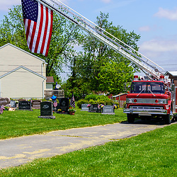 New Holland, PA, USA / May 25, 2020: A parked ladder truck flies the American flag over the grave of hometown hero Chad Burkhart, a US Navy Seal Petty Officer killed in Kosovo in 2020.