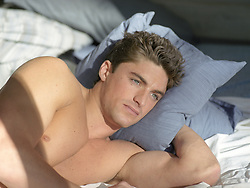 good looking man deep in thought while in bed